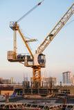 Grues de construction industrielles, et bâtiment en construction de site dans la ville Photographie stock