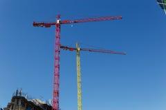 Grues de construction modernes devant le ciel bleu Photo stock