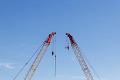 Grues de construction modernes devant le ciel bleu Image libre de droits