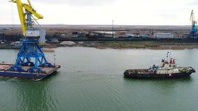 Grues de remorquage pour des récipients Grand navire porte-conteneurs tiré en des remorqueurs De dessus vue aérienne vers le bas  Photo stock