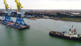 Grues de remorquage pour des récipients Grand navire porte-conteneurs tiré en des remorqueurs De dessus vue aérienne vers le bas  Image stock