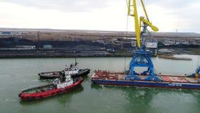 Grues de remorquage pour des récipients Grand navire porte-conteneurs tiré en des remorqueurs De dessus vue aérienne vers le bas  Photographie stock