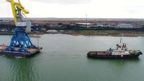 Grues de remorquage pour des récipients Grand navire porte-conteneurs tiré en des remorqueurs De dessus vue aérienne vers le bas  Photos libres de droits