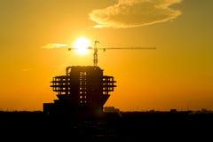 Grues et bâtiments en construction contre le coucher de soleil Photos libres de droits