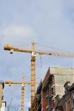 Grues et maison jaunes en construction au centre du vieux centre de la ville Images stock