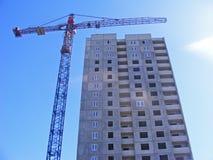 Grues et nouveau bâtiment sur un ciel bleu de fond Image stock