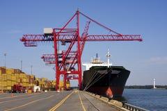 Grues gauches de conteneur déchargeant un bateau Image stock
