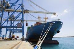 Grues par des récipients de cargaison dans le bateau Photos stock