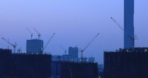 Grues sur le bâtiment à l'en construction dans Ariake Tokyo au crépuscule clips vidéos