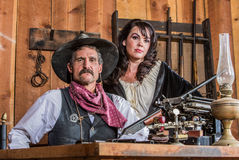 Gruff Cowboy Poses With Saloon Girl Stock Images