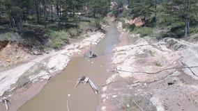 Gruis die de werken aangaande smalle modderige rivieroppervlakte halen stock videobeelden