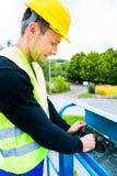 Gruista che guida rampa di sollevamento idraulica con il banco di comando Fotografia Stock Libera da Diritti