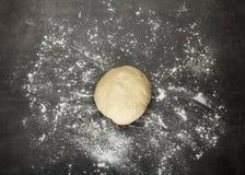 Grumo di pasta sulla superficie di lavoro spruzzata con farina immagine stock