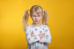Grumpy angry Caucasian blonde girl with blue eyes in white dress posing in studio on yellow background royalty free stock photography