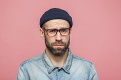Grumpy bearded man with offended expression, being dissatisfied with something, frowns face, wears spectacles, hat and shirt, isol stock photos