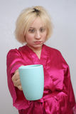 Grumpy Blonde Holds Out Her Coffee Cup. A disheveled blonde with a grouchy facial expression, wearing a bathrobe, extends a coffee cup. Selective focus on the royalty free stock photos