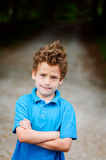 Grumpy boy. Young boy looking angry with arms crossed Royalty Free Stock Photos
