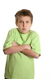 Grumpy Child. Ill-tempered or grumpy child with arms crossed and looking very stubborn Stock Photo