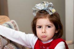 Grumpy Christmas Girl. A grumpy, pouty faced girl on Christmas morning.  She has a big, silver bow on her head and her bottom lip is sticking out with her Royalty Free Stock Photography