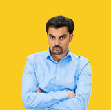 Grumpy. Closeup portrait, displeased, pissed off, angry, grumpy business man, bad attitude, arms crossed, folded, looking at you, isolated yellow background Royalty Free Stock Photo