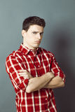 Grumpy depressed young sportsman crossing his arms for boredom. Grumpy depressed young sportsman with checked shirt crossing his arms for disappointment, boredom Royalty Free Stock Images