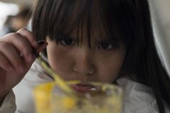Grumpy face. A little girl starring at a glass of juice with a grumpy face Stock Image
