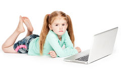 Grumpy Girl With Laptop Computer. Small girl with laptop looking grumpy. Studio on white background Royalty Free Stock Photography