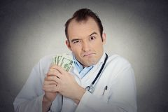 Grumpy greedy miserly health care professional holding money Stock Images