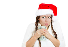 Grumpy greedy miserly young woman wearing red santa claus hat protecting money, dollar bills in hand, looking anxiously to the sid Royalty Free Stock Photos