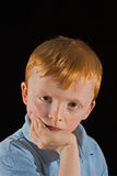 Grumpy kid. Boy looking grumping against a black background Royalty Free Stock Image