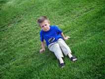 Grumpy kid in grass. A grumpy boy sitting and pouting in a field of grass Royalty Free Stock Images