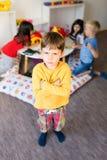 Grumpy in kindergarten. Portrait of frustrated boy in kindergarten Stock Image