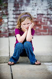 Grumpy Little Girl Sitting on Curb Royalty Free Stock Images