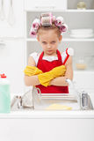 Grumpy little girl washing dishes Royalty Free Stock Photos