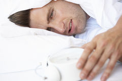 Grumpy Man In Bed Turning Off Alarm Clock Royalty Free Stock Photos