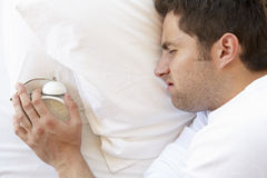 Grumpy Man In Bed Turning Off Alarm Clock Royalty Free Stock Images