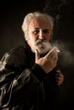 Grumpy man with cigarette. Against black background Royalty Free Stock Images