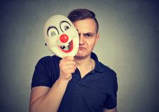 Grumpy man covering personality with mask stock photo