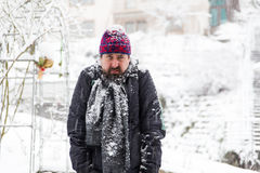 Grumpy man in a snowy garden Stock Photos