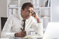 Grumpy man working on project. Grumpy african american businessman working on project at office desk with laptop, notepad and smartphone. Shelf with documents in Stock Photo