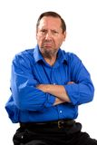 Grumpy Moody Senior. Man sits with his arms crossed and an unhappy expression on his face stock photos