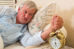 Grumpy morning temper. Bad tempered grumpy old man in bed Royalty Free Stock Photography