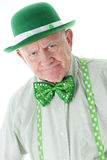 Grumpy Old Irish Man. Closeup image of a grumpy senior man dressed all in green.  His suspenders and hat are adorned with shamrocks.  On a white background Royalty Free Stock Photo