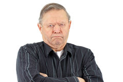 Grumpy old man. Senior man with arms crossed looking very grumpy, unhappy or mad Royalty Free Stock Image