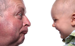 Grumpy Old Man and Happy Baby Boy. Little Baby Boy Laughing At Aged Man In His Face Royalty Free Stock Image