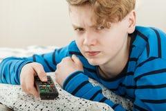 Grumpy petulant teenage boy watching television Stock Photo