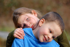 Grumpy Sad Sister. Grumpy sad big sister is holding onto smiling and content little brother in this cute sibling photo Royalty Free Stock Photography