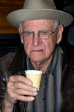 Grumpy senior before his morning coffee. An grumpy 88 year old man not liking his sample cup of coffee Stock Image