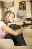 Grumpy Teenage Daughter Sitting On Sofa With Mother In Background Stock Images