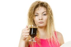 Tired woman drinking her morning coffee. Grumpy tired woman holding black coffee about to drink. Hard morning, getting energy Royalty Free Stock Photography